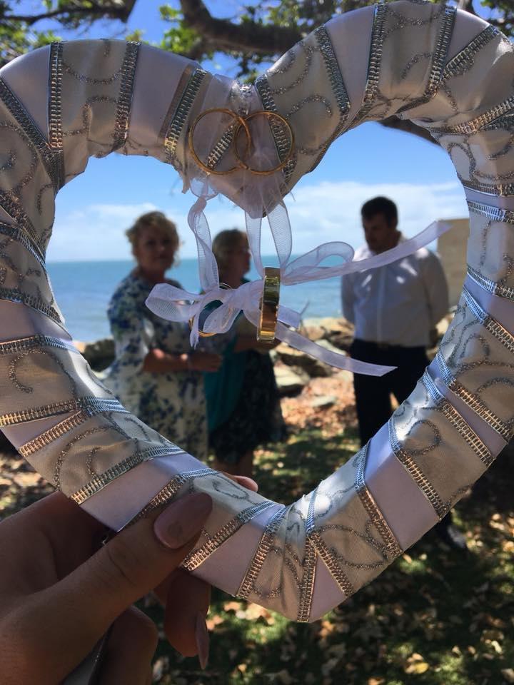 beach wedding image with handcrafted love heart and wedding rings tied to it