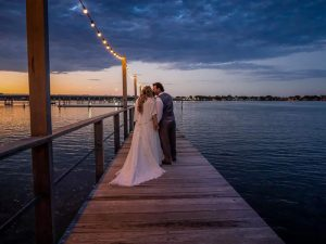 bride and groom on the pier with the sun setting and water backdrop on their wedding day