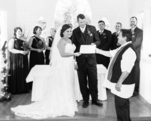 black and white image of bride and groom at the alter with the marriage celebrant