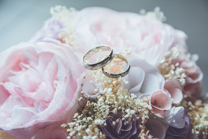 2 wedding rings on flower arrangement