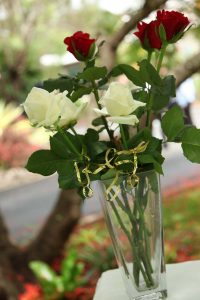 Rose and ring wedding ceremony image showing a vase with white and red roses