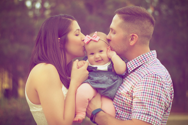 baby naming ceremony image of both parents kissing their baby daughter on her naming day