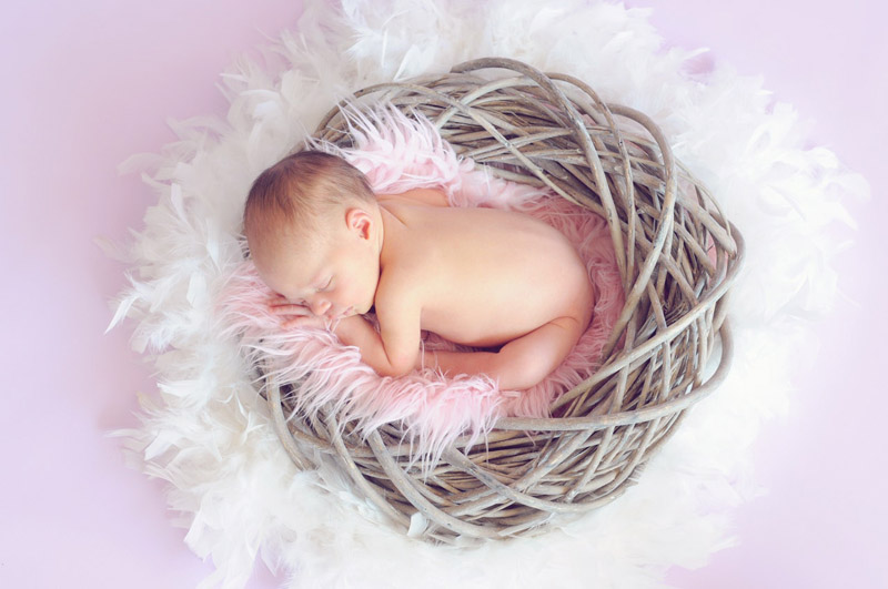 baby naming ceremony image of baby-sleeping-in-a-basket-and-a-round-feather-surrounding