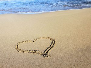 a love heart drawn in the sand at at wedding photo shoot on the beach