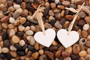 2 love hearts placed on pebbles for wedding ceremony