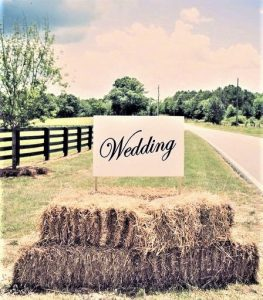 hints and tips for planning your wedding ceremony image of a hay bale with wedding sign