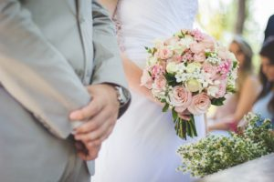 hints and tips planning the wedding ceremony image of bride and groom at the alter with bride holding a bouquet of flowers
