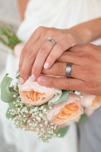 renewal of wedding vows image showing 2 hands on flowers with wedding rings on fingers